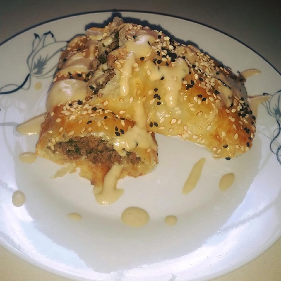 בורקס פילו ממולא בבשר ופיטריות מצופה בקצח ושומשום בזילוף טחינה